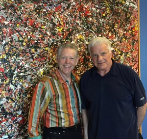 Jim White (L) and Phil Romano in front of one of the prolific artist's paintings.